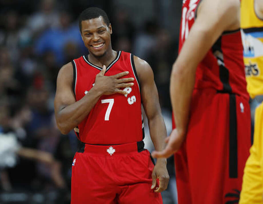 Toronto Raptors guard Kyle Lowry smiles as he takes the court after greeting members of the Denver Nuggets in the first half of an NBA basketball game Friday, Nov. 18, 2016, in Denver. (AP Photo/David Zalubowski)