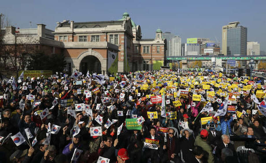 "Protesters supporting South Korean President Park Geun-hye wave national flags and placards during a rally opposing her resignation in Seoul, South Korea, Saturday, Nov. 19, 2016. For the fourth straight weekend, masses of South Koreans were expected to descend on major avenues in downtown Seoul demanding an end to the presidency of Park, who prosecutors plan to question soon over an explosive political scandal. The letters on placards read: ""Constitution Protection"" and ""Opposition to her Resignation."" (AP Photo/Lee Jin-man)"