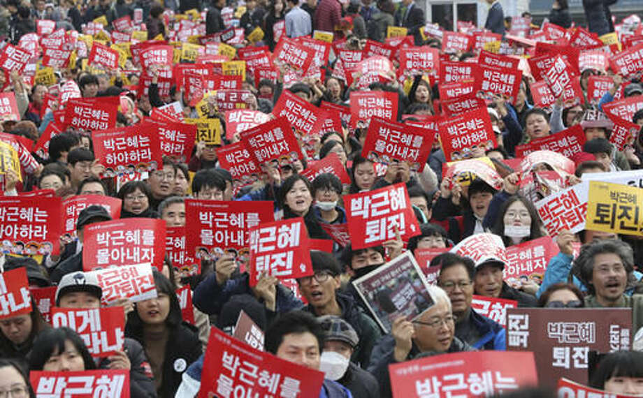 """South Korean protesters hold up cards during a rally calling for South Korean President Park Geun-hye to step down in Seoul, South Korea, Saturday, Nov. 19, 2016. For the fourth straight weekend, masses of South Koreans were expected to descend on major avenues in downtown Seoul demanding an end to the presidency of Park, who prosecutors plan to question soon over an explosive political scandal. The letters read """"Park Geun-hye should step down."""" (AP Photo/Lee Jin-man)"""