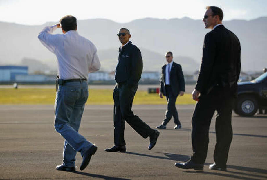 President Barack Obama walk across the tarmac after stepping off Air Force One during a refueling stop at Lajes Field, Azores on the island of Terceira, Friday, Nov. 18, 2016. Obama left Europe and is heading to South America to attend the annual Asia Pacific Economic Cooperation (APEC) forum, taking place in Lima, Peru. (AP Photo/Pablo Martinez Monsivais)