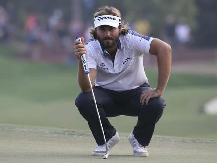 Victor Dubuisson of France studies his play on the 18th hole during the 3rd round of the DP World Tour Championship golf tournament at the Jumeirah Golf Estates in Dubai, United Arab Emirates, Saturday, Nov. 19, 2016. (AP Photo/Kamran Jebreili)