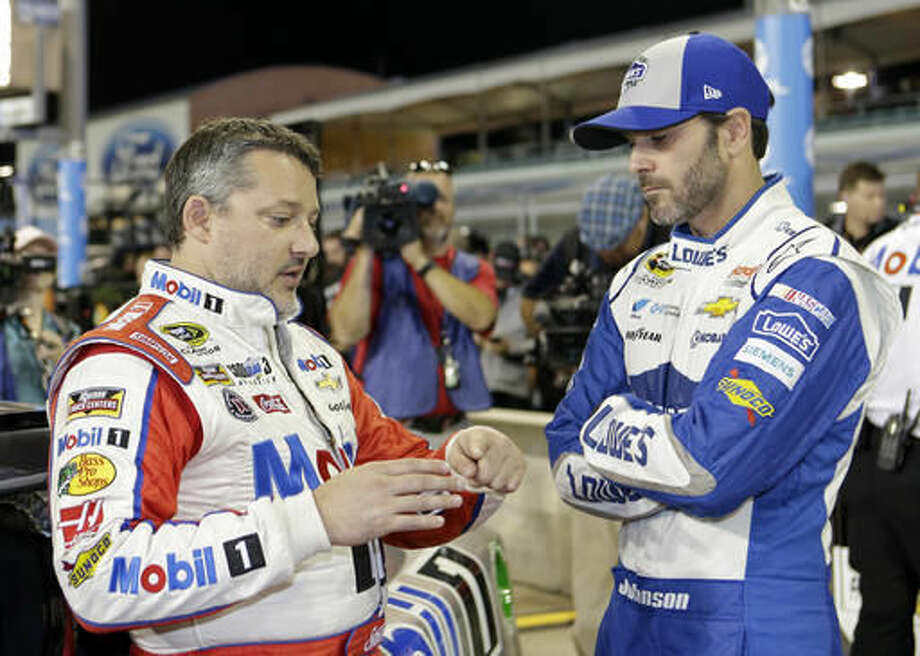 Race drivers Tony Stewart, left, and Jimmie Johnson talk before the NASCAR Sprint Cup Series Auto Racing qualifying Friday, Nov. 18, 2016, in Homestead, Fla. (AP Photo/Alan Diaz)