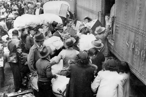 Hundreds of Japanese-Americans, allowed to keep only the belongings that they can carry, are forced onto trains bound for relocation centers Internment camps