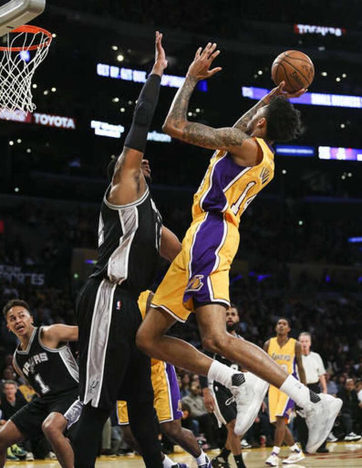 Los Angeles Lakers forward Brandon Ingram shoots as San Antonio Spurs forward LaMarcus Aldridge defends during the first half of an NBA basketball game Friday, Nov. 18, 2016, in Los Angeles. (AP Photo/Ringo H.W. Chiu)