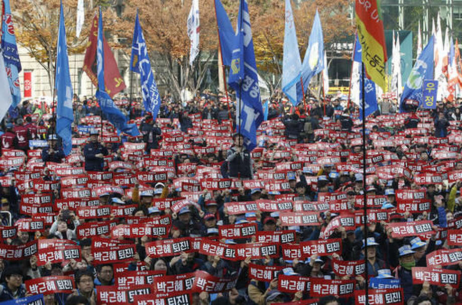 "South Korean protesters hold up cards during a rally calling for South Korean President Park Geun-hye to step down in Seoul, South Korea, Saturday, Nov. 19, 2016. For the fourth straight weekend, masses of South Koreans were expected to descend on major avenues in downtown Seoul demanding an end to the presidency of Park, who prosecutors plan to question soon over an explosive political scandal. The letters read ""Park Geun-hye should step down"". (AP Photo/Ahn Young-joon)"