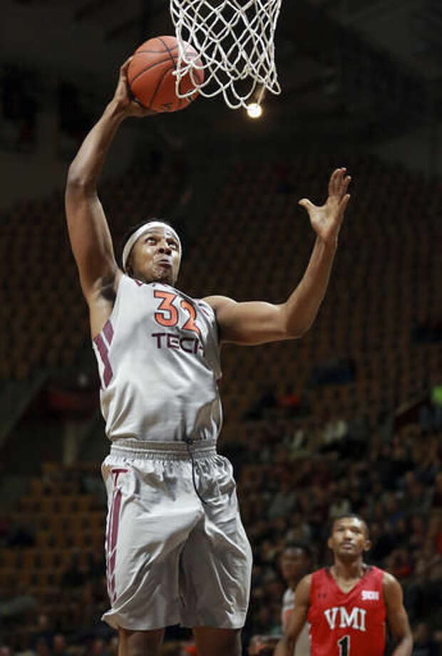 Virginia Tech's Zach LeDay (32) dunks as Virginia Military Institute's Keith Smith (1) watches during the second half of an NCAA college basketball game in Blacksburg, Va., Saturday, Nov. 19, 2016. (Matt Gentry/The Roanoke Times via AP)