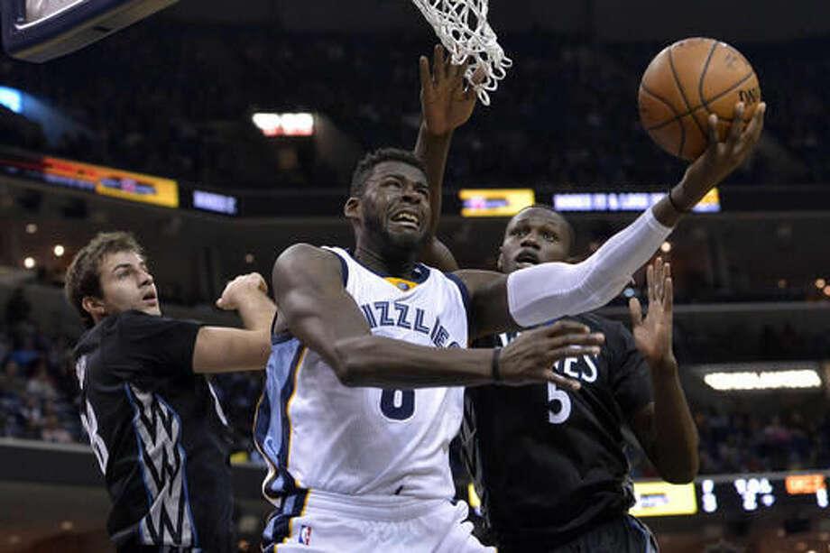 Memphis Grizzlies forward James Ennis, center, shoots between Minnesota Timberwolves forwards Gorgui Dieng (5) and Nemanja Bjelica (88) in the second half of an NBA basketball game Saturday, Nov. 19, 2016, in Memphis, Tenn. (AP Photo/Brandon Dill)