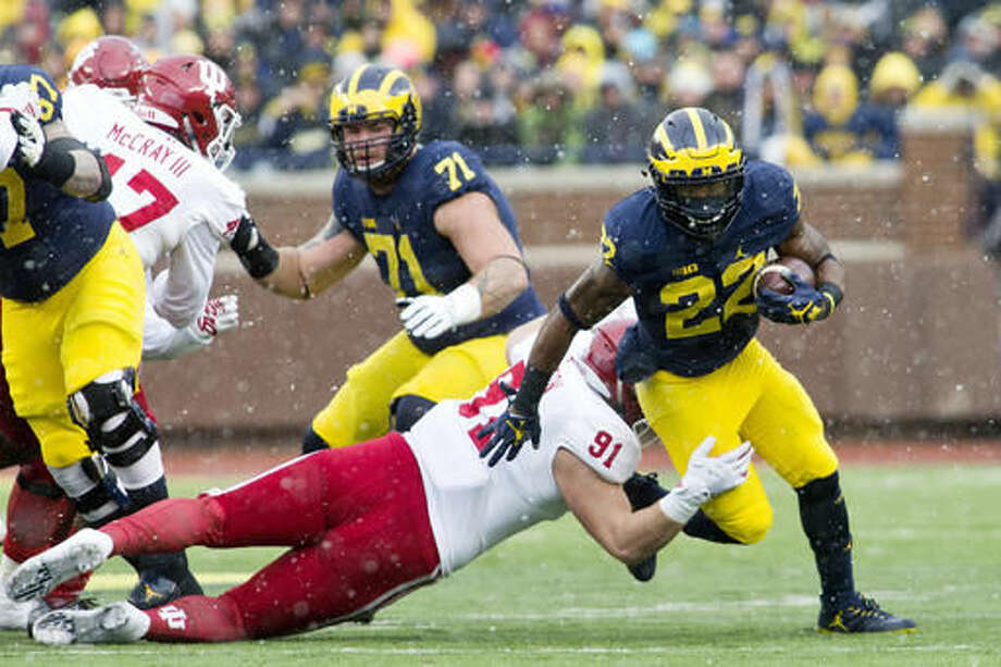 Michigan running back Karan Higdon (22) try to evade a tackle from Indiana defensive lineman Jacob Robinson (91) in the first quarter of an NCAA college football game in Ann Arbor, Mich., Saturday, Nov. 19, 2016. (AP Photo/Tony Ding)