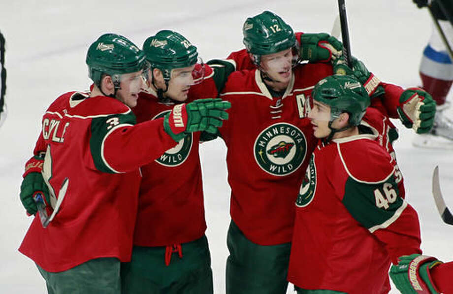Minnesota Wild teammates Charlie Coyle, Nino Niederreiter, of Switzerland, Eric Staal, and Jared Spurgeon celebrate Coyle's power play goal during the first period of an NHL hockey game against the Colorado Avalanche, Saturday, Nov. 19, 2016, in St. Paul, Minn. (AP Photo/Paul Battaglia)