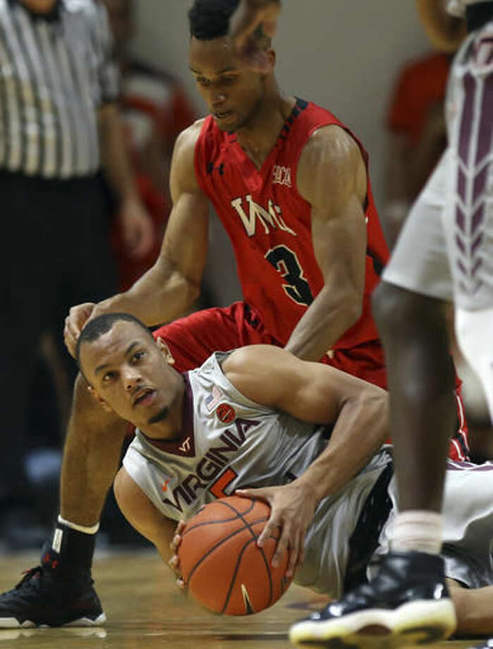 Virginia Tech's Justin Robinson (5) looks to pass after recovering a loose ball in front of Virginia Military's Adrian Rich (3) in the first half of an NCAA college basketball game, Saturday, Nov. 19, 2016 in Blacksburg, Va. (Matt Gentry/The Roanoke Times via AP)