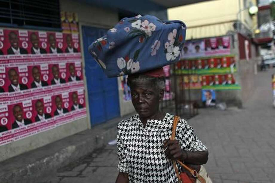 A woman walks past a polling station covered with campaign posters promoting presidential candidates, in Port-au-Prince, Haiti, Saturday, Nov. 19, 2016. Sunday's voters will choose a president, with the top two finishers going to a Jan. 29 runoff, as well as senators and members of the Chamber of Deputies. (AP Photo/Ricardo Arduengo)