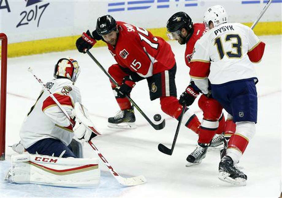 Ottawa Senators' Zack Smith (15) and Derick Brassard (19) attempt to control the puck as Florida Panthers goaltender Roberto Luongo (1) and Panthers' Mark Pysyk (13) defend during the third period of an NHL hockey game in Ottawa, Ontario, Saturday, Nov. 19, 2016. (Fred Chartrand/The Canadian Press via AP)