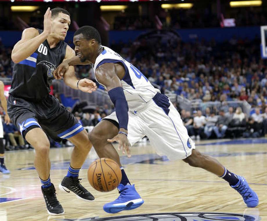 Dallas Mavericks' Harrison Barnes, right, goes to the basket against Orlando Magic's Aaron Gordon during the first half of an NBA basketball game, Saturday, Nov. 19, 2016, in Orlando, Fla. (AP Photo/John Raoux)