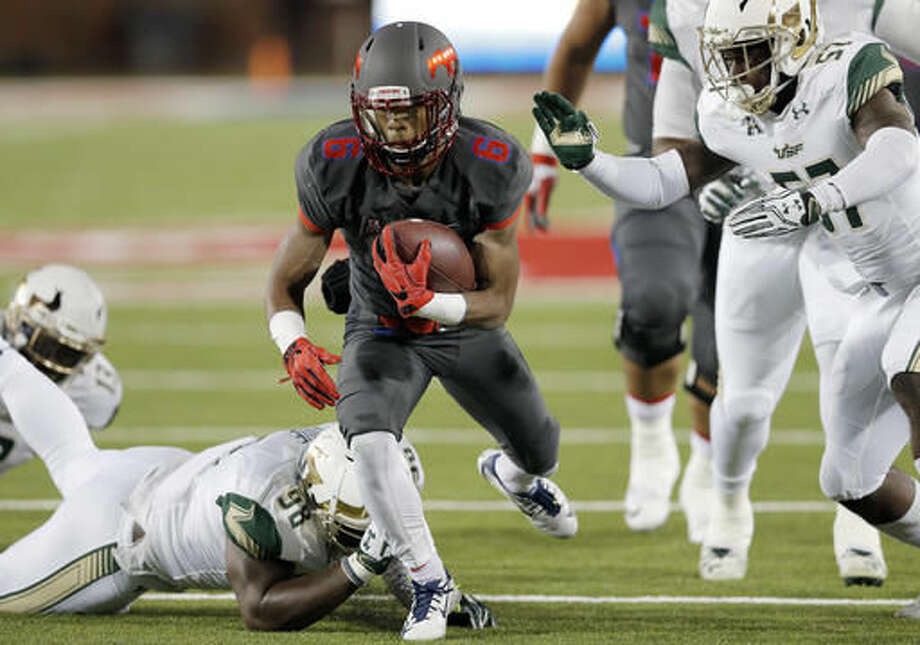 SMU running back Braeden West (6) battles past South Florida defensive end Mike Love (98) and linebacker Nigel Harris (57) during the first half of an NCAA college football game Saturday, Nov. 19, 2016, in Dallas. (AP Photo/Brandon Wade)