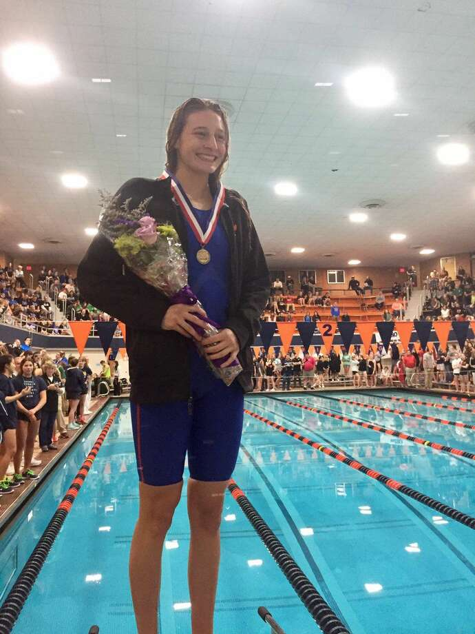 Edwardsville senior Bailey Grinter smiles on the medal stand on Saturday after winning the 100-yard backstroke at the state meet at Evanston High School.