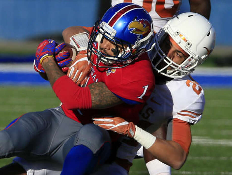 Kansas wide receiver LaQuvionte Gonzalez (1) is tackled by Texas cornerback John Bonney (24) during the first half of an NCAA college football game in Lawrence, Kan., Saturday, Nov. 19, 2016. (AP Photo/Orlin Wagner)