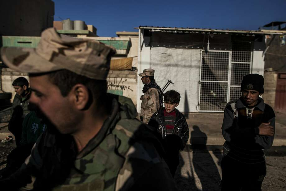 Young men stand near Iraqi Army soldiers near the front lines in Shyma district in Mosul, the country's second largest city. Photo: Manu Brabo, Associated Press