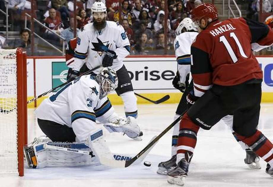 San Jose Sharks goalie Martin Jones, left, makes a save on a shot by Arizona Coyotes center Martin Hanzal (11) as Sharks defenseman Brent Burns (88) and defenseman Justin Braun (61) look on during the second period of an NHL hockey game Saturday, Nov. 19, 2016, in Glendale, Ariz. (AP Photo/Ross D. Franklin)