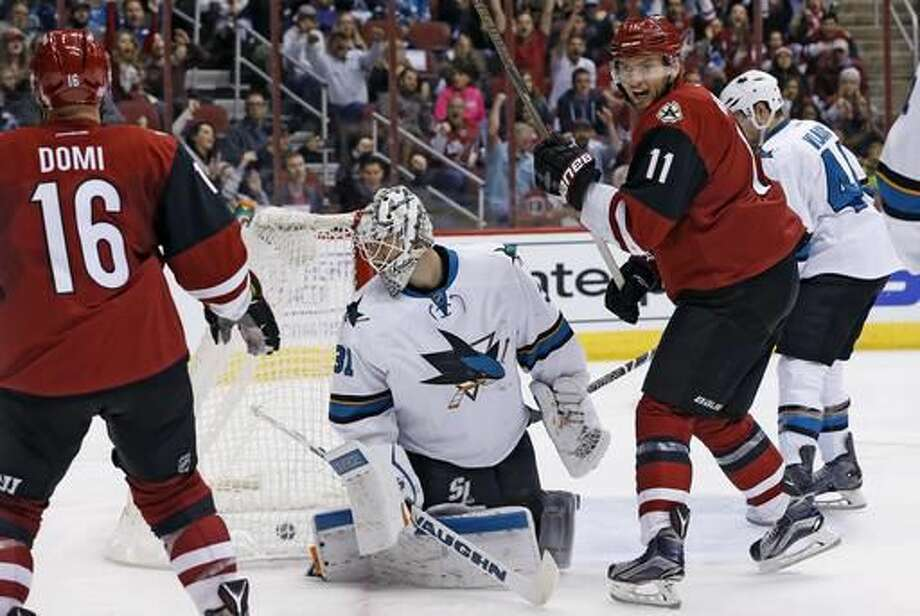 Arizona Coyotes center Martin Hanzal (11) celebrates a goal by teammate left wing Max Domi (16) against San Jose Sharks goalie Martin Jones (31) during the second period of an NHL hockey game Saturday, Nov. 19, 2016, in Glendale, Ariz. (AP Photo/Ross D. Franklin)