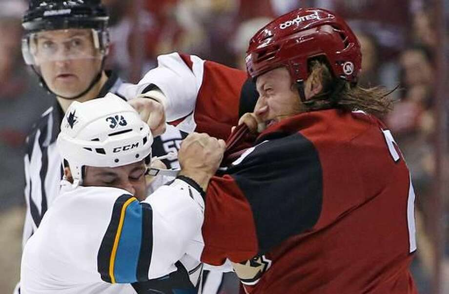 Arizona Coyotes center Ryan White, right, exchange punches with San Jose Sharks center Micheal Haley (38) as they fight during the first period of an NHL hockey game Saturday, Nov. 19, 2016, in Glendale, Ariz. (AP Photo/Ross D. Franklin)