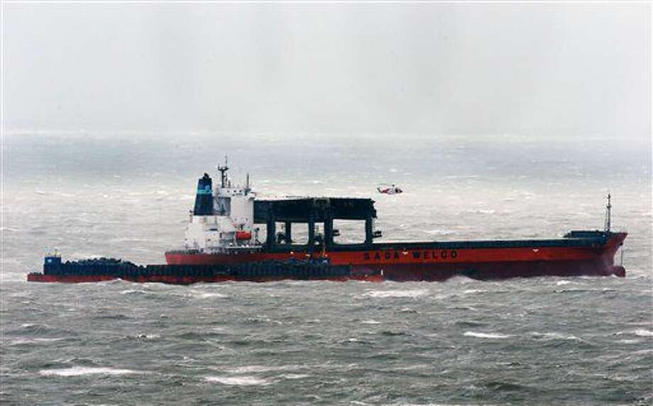 A coastguard helicopter attends the scene where some crew members are being removed from the cargo ship that is taking on water in the English Channel, as a storm, Storm Angus, the year's first big winter storm in Britain, lashes England's south coast, Sunday Nov. 20, 2016. Forecasters say winds of 68 mph (110 kph) hit the south coast early Sunday, with a gust of 97 mph (156 kph) recorded offshore. (Gareth Fuller/PA via AP)