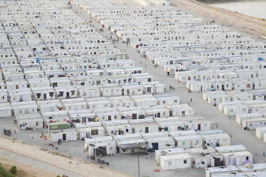 """This undated photo provided by MoMA shows a photograph of Nizip II, a Container Camp in Turkey on the Syrian border. The photograph is part of the exhibit """"Insecurities: Tracing Displacement and Shelter,"""" at the museum in New York. The new exhibit invites visitors to take an entirely new look at the concept of home and design, this time through the lens of migration and global refugee emergencies, in which temporary shelters, organizers say, are being deployed on a scale akin to that after World War I. (Tobias Hutzler/MoMA via AP)"""