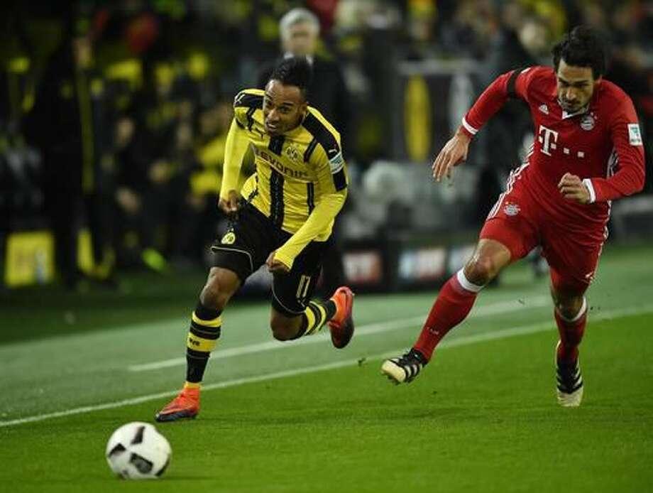 Dortmund's Pierre-Emerick Aubameyang, left, runs faster than Bayern's Mats Hummels, during the German Bundesliga soccer match between Borussia Dortmund and Bayern Munich in Dortmund, Germany, Saturday, Nov. 19, 2016. (AP Photo/Martin Meissner)