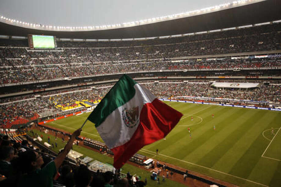 FILE - In this June 11, 2013, file photo, a fan waves Mexico's national flag during Mexico's World Cup qualifying soccer match with Costa Rica in Azteca Stadium in Mexico City. The Houston Texans and the Oakland Raiders are scheduled to play an NFL football game at the stadium Monday night. (AP Photo/Ivan Pierre Aguirre, File)