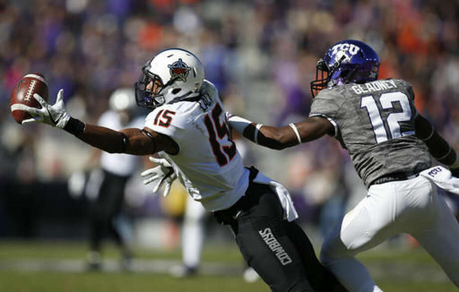 Oklahoma State wide receiver Chris Lacy, right, attempts a catch in front of TCU cornerback Jeff Gladney (12) during the first half of an NCAA college football game, Saturday, Nov. 19, 2016, in Fort Worth, Texas. Gladney was called for pass interference on the play. (AP Photo/Jim Cowsert)