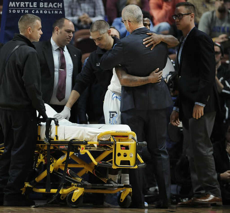 Rhode Island's Jarvis Garrett hugs head coach Dan Hurley before he leaves the arena on a stretcher in the first half of an NCAA college basketball game against Cincinnati, Saturday, Nov. 19, 2016, in Uncasville, Conn. (AP Photo/Jessica Hill)