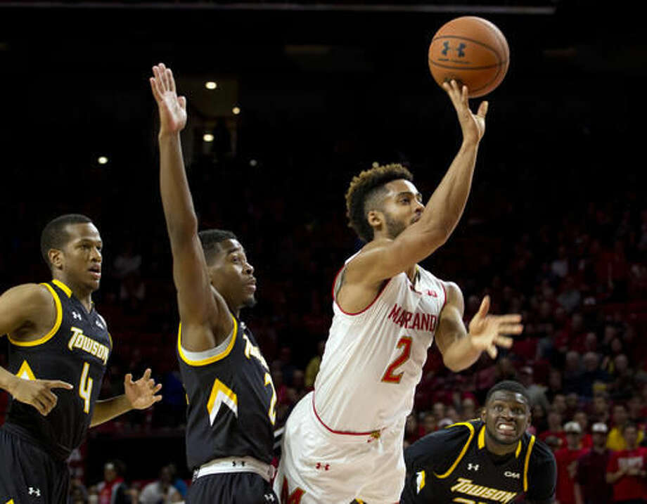 Maryland's Melo Trimble (2) shoots to the basket as Towson's Jordan Mcneil (2) defends him during the first half of an NCAA college basketball game, Sunday, Nov. 20, 2016, in College Park, Md. (AP Photo/Jose Luis Magana)