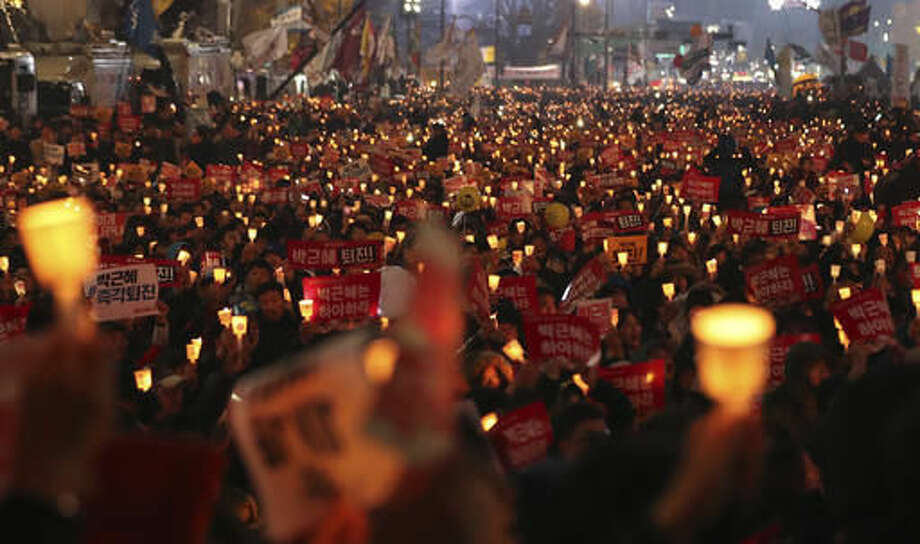 """South Korean protesters hold up candles during a rally calling for South Korean President Park Geun-hye to step down in Seoul, South Korea, Saturday, Nov. 19, 2016. For the fourth straight Saturday, masses of South Koreans filled major avenues in downtown Seoul demanding an end to the presidency of Park, who prosecutors plan to question soon over an explosive political scandal. The letters read """"Park Geun-hye, Step Down."""" (AP Photo/Lee Jin-man)"""