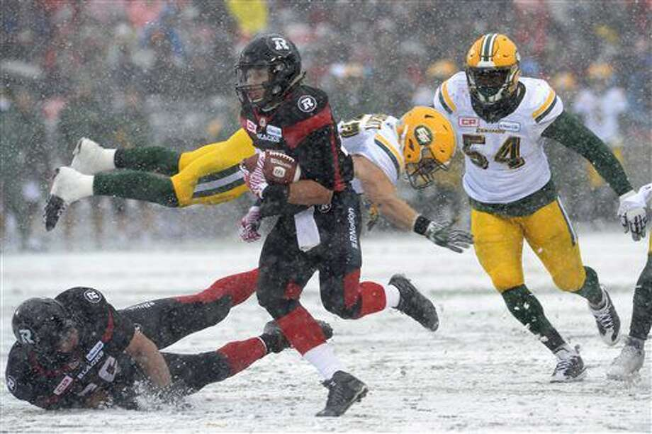 Ottawa Redblacks' Greg Ellingson, center, dodges the Edmonton Eskimos defenders J.C. Sherritt, Center back, and Phillip Hunt (54) on his way to scoring a touchdown during the first half of a CFL eastern final football game in Ottawa, Ontario, Sunday, Nov. 20, 2016. (Adrian Wyld/The Canadian Press via AP)