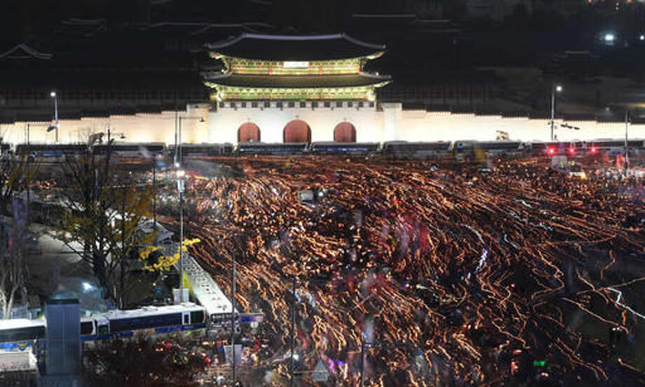 In this photo taken with a long exposure time, tens of thousands of South Korean protesters with candles march in front of Gwanghwamun, the main gate to the royal Gyeongbokgung Palace of the Joseon dynasty on their way to the presidential Blue House during a rally calling for South Korean President Park Geun-hye to step down in Seoul, South Korea, Saturday, Nov. 19, 2016. For the fourth straight weekend, masses of South Koreans were expected to descend on major avenues in downtown Seoul demanding an end to the presidency of Park, who prosecutors plan to question soon over an explosive political scandal. (Jung Yeon-je/Pool Photo via the AP)