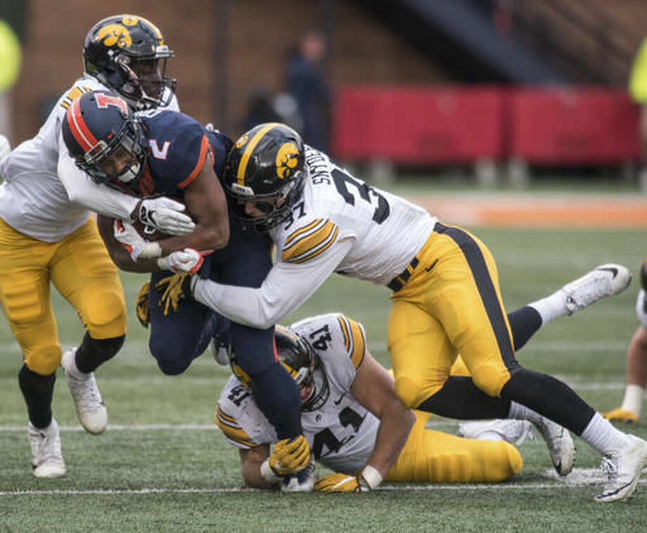 Illinois running back Reggie Corbin (2) is tackled by Iowa defensive backs Manny Rugamba (5) and Brandon Snyder (37), and linebacker Bo Bower (41) during the second quarter of an NCAA college football game Saturday, Nov. 19, 2016, at Memorial Stadium in Champaign, Ill. (AP Photo/Bradley Leeb)