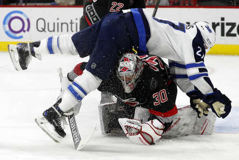 Winnipeg Jets' Quinton Howden (21) collides with Carolina Hurricanes goalie Cam Ward (30) as he tries to make a save during the first period of an NHL hockey game, Sunday, Nov. 20, 2016, in Raleigh, N.C. (AP Photo/Karl B DeBlaker)