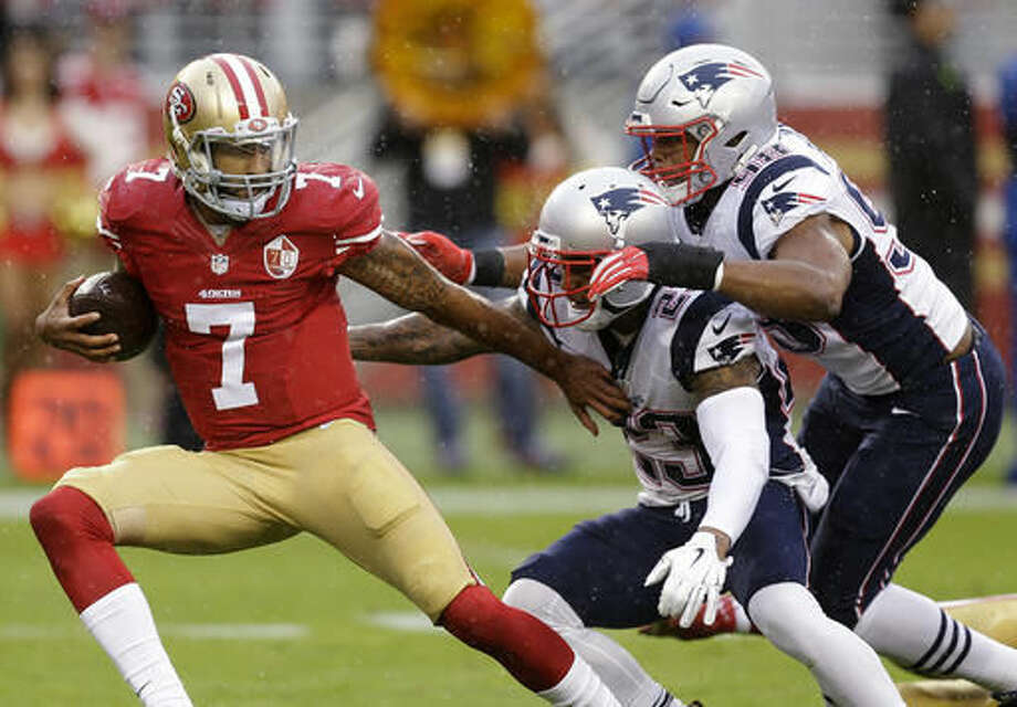 San Francisco 49ers quarterback Colin Kaepernick (7) tries to escape from New England Patriots strong safety Patrick Chung (23) and defensive end Trey Flowers (98) before Chung sacked him during the first half of an NFL football game in Santa Clara, Calif., Sunday, Nov. 20, 2016. (AP Photo/Ben Margot)