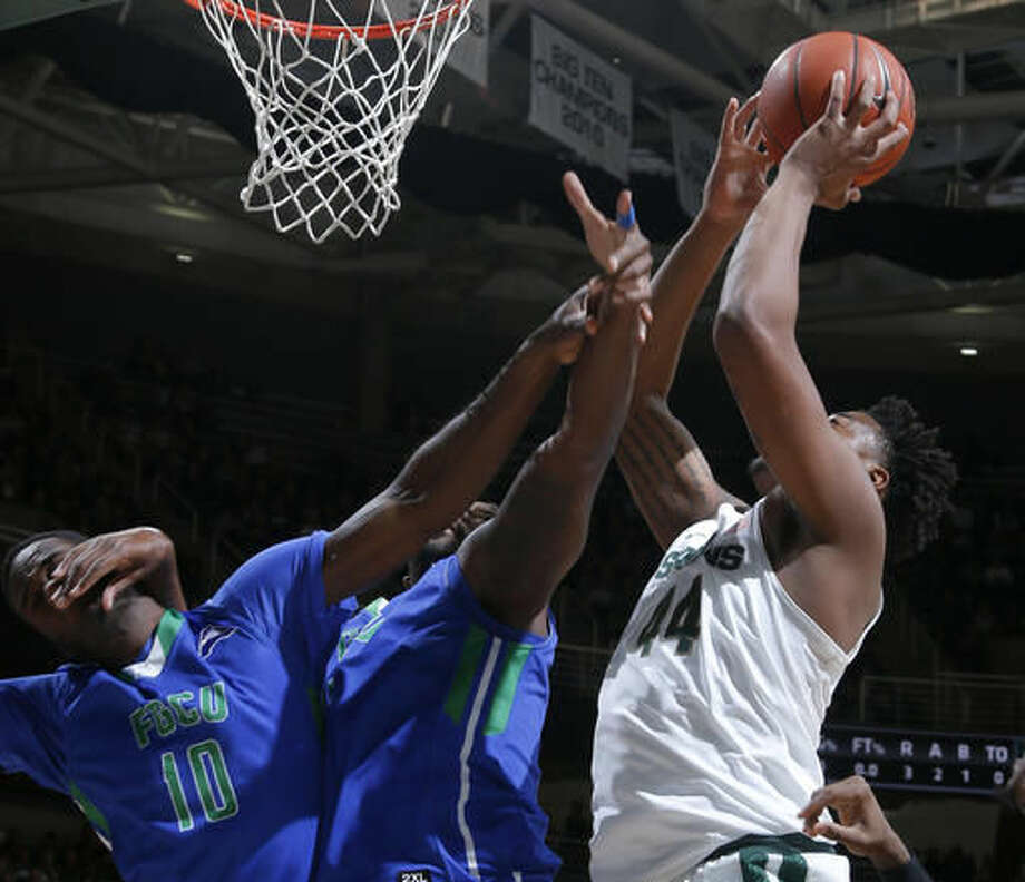 Michigan State's Nick Ward, right, and Florida Gulf Coast's Kevin Mickle (10) and Antravious Simmons, center, battle for a rebound during the first half of an NCAA college basketball game, Sunday, Nov. 20, 2016, in East Lansing, Mich. (AP Photo/Al Goldis)