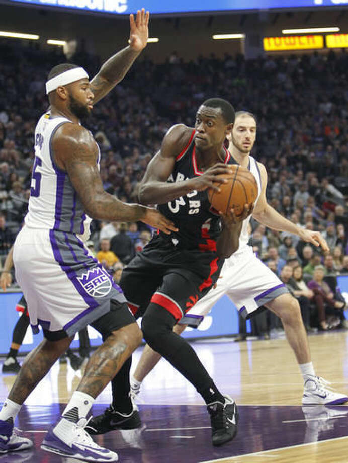 Toronto Raptors forward Pascal Siakam (43) looks for an opening around Sacramento Kings defender DeMarcus Cousins during the first half of an NBA basketball game in Sacramento, Calif., Sunday, Nov. 20, 2016. (AP Photo/Steve Yeater)
