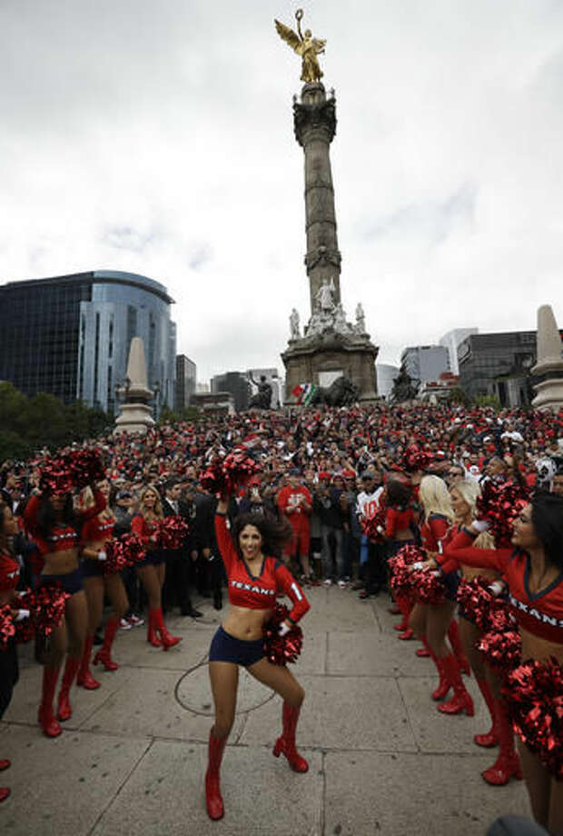 Houston Texans cheerleaders perform in front of the Angel of Independence monument in Mexico City, Sunday, Nov. 20, 2016. The Texans face the Oakland Raiders in an NFL football game in Mexico City on Nov. 21. (AP Photo/Gregory Bull)