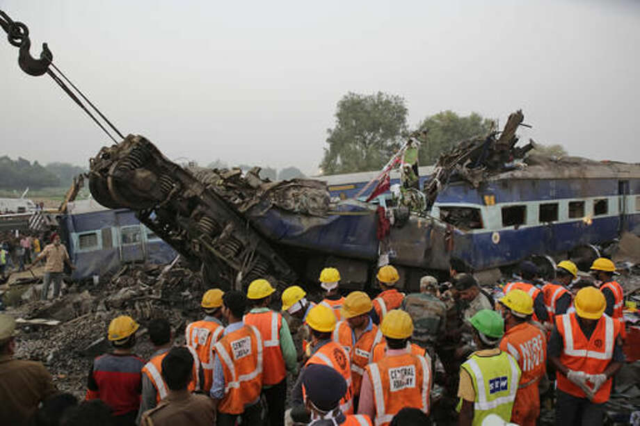 FILE- In this Nov. 20, 2016 file photo, rescuers search in the debris after 14 coaches of an overnight passenger train rolled off the track near Pukhrayan village Kanpur Dehat district, Uttar Pradesh state, India. For more than 150 years, India's sprawling rail network has helped knit this disparate country together. But every year, those trains also kill more than 15,000 people. The Indian rail network lacks modern signaling and communication systems, and is hobbled by poor maintenance and staffing problems.(AP Photo/Rajesh Kumar Singh, File)