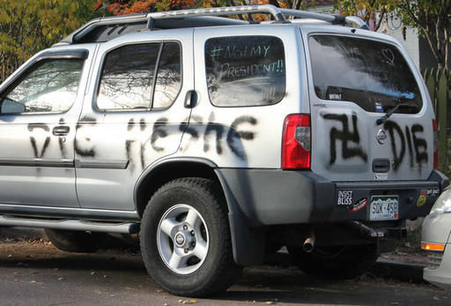 """This Wednesday, Nov. 16, 2016 photo provided by Denverite.com shows spray painted anti-transgender graffiti on the car of Amber Timmons, a transgender woman, in Denver. After the sweeping Republican election victory on Nov. 9, 2016, transgender people """"are concerned for their safety, survival and legal rights in the coming years,"""" said Chase Strangio, an attorney with the American Civil Liberties Union who often works on transgender issues. (Ashley Dean/Denverite.com via AP)"""