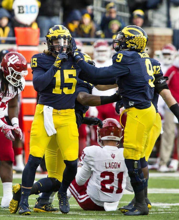 Michigan defensive end Chase Winovich (15) celebrates with linebacker Mike McCray (9) after sacking Indiana quarterback Richard Lagow (21) during the first quarter of an NCAA college football game in Ann Arbor, Mich., Saturday, Nov. 19, 2016. Michigan won 20-10. (AP Photo/Tony Ding)