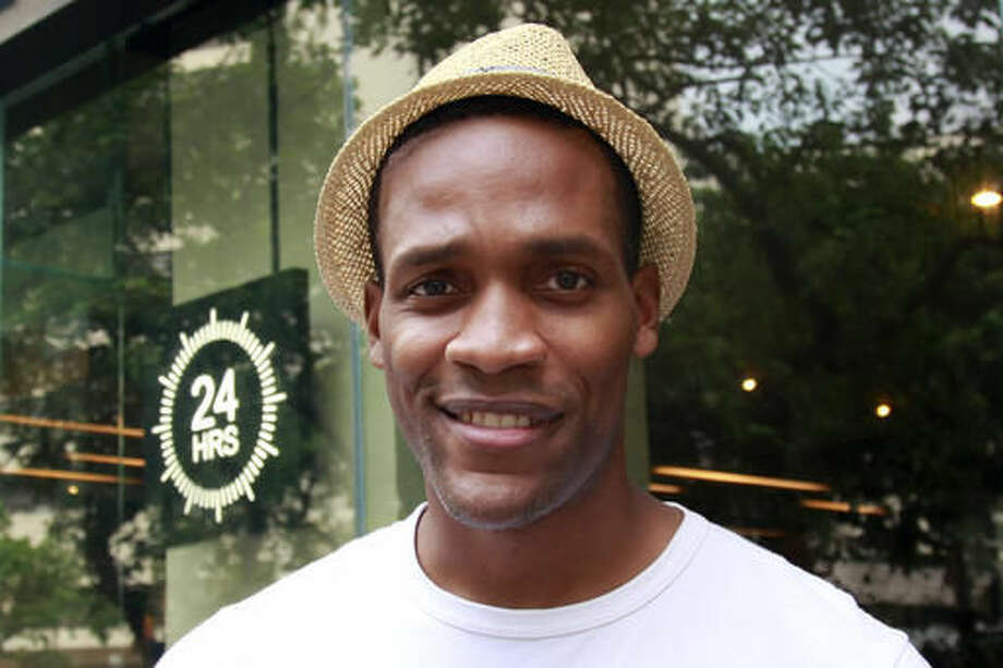 "In this Aug. 10, 2016 photo, New Yorker Mekael Turner stands outside a cafe in Guangzhou in southern China's Guangdong province. Turner has been in China for 13 years and when he first landed in Guangzhou, the capital of Guangdong, with a plan to ""learn Cantonese and do Hong Kong movies."" everyone suggested he first learn Mandarin. (AP Photo/Louise Watt)"