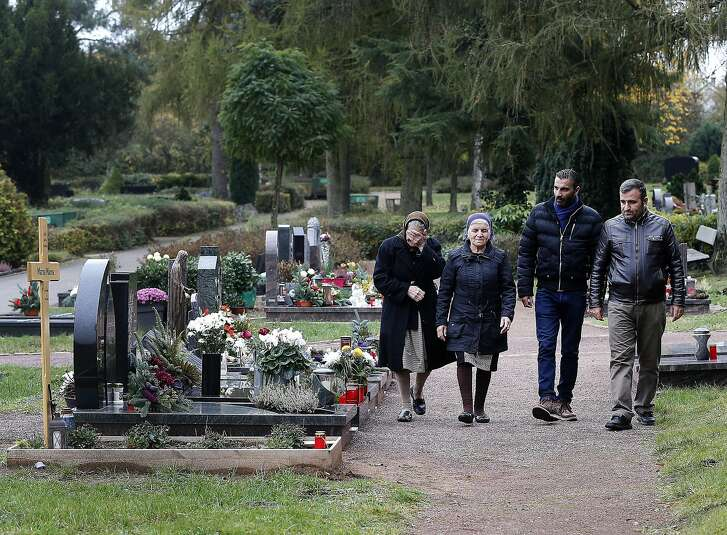 Sherineh Marza, Zammo Marza, Charli Kanoun and Abdo Marza, from left, go to the grave of Marza Marza in Saarlouis, Germany in this Monday, Nov. 7, 2016 photo. The Marza family were among 226 Assyrian Christians taken captive by the Islamic State group in a February 2015 attack on their villages in northern Syria. It took a year to free the hostages, and only after three were killed and millions of dollars gathered by the Assyrian diaspora worldwide was paid to the militants. (AP Photo/Michael Probst)