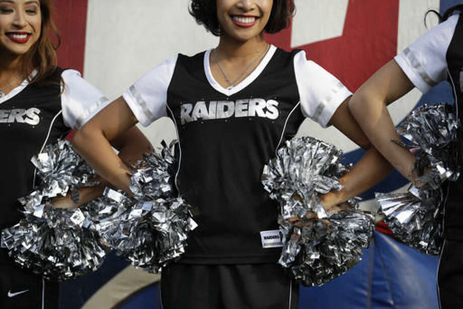 Oakland Raiders cheerleaders look on during an NFL-sponsored event promoting physical activity in children, in Mexico City, Friday, Nov. 18, 2016. The NFL's Play 60 campaign encourages children to be active 60 minutes a day to avoid childhood obesity. The Raiders play the Houston Texans on Monday. (AP Photo/Rebecca Blackwell)
