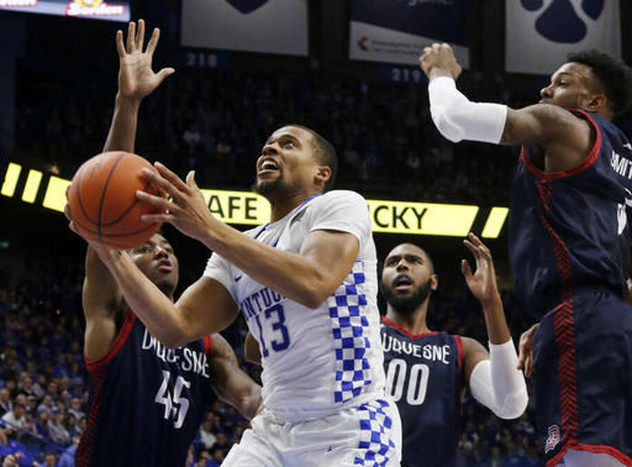 Kentucky's Isaiah Briscoe (13) shoots between Duquesne's Isiaha Mike, left, Darius Lewis (00) and Tarin Smith during the second half of an NCAA college basketball game, Sunday, Nov. 20, 2016, in Lexington, Ky. (AP Photo/James Crisp)