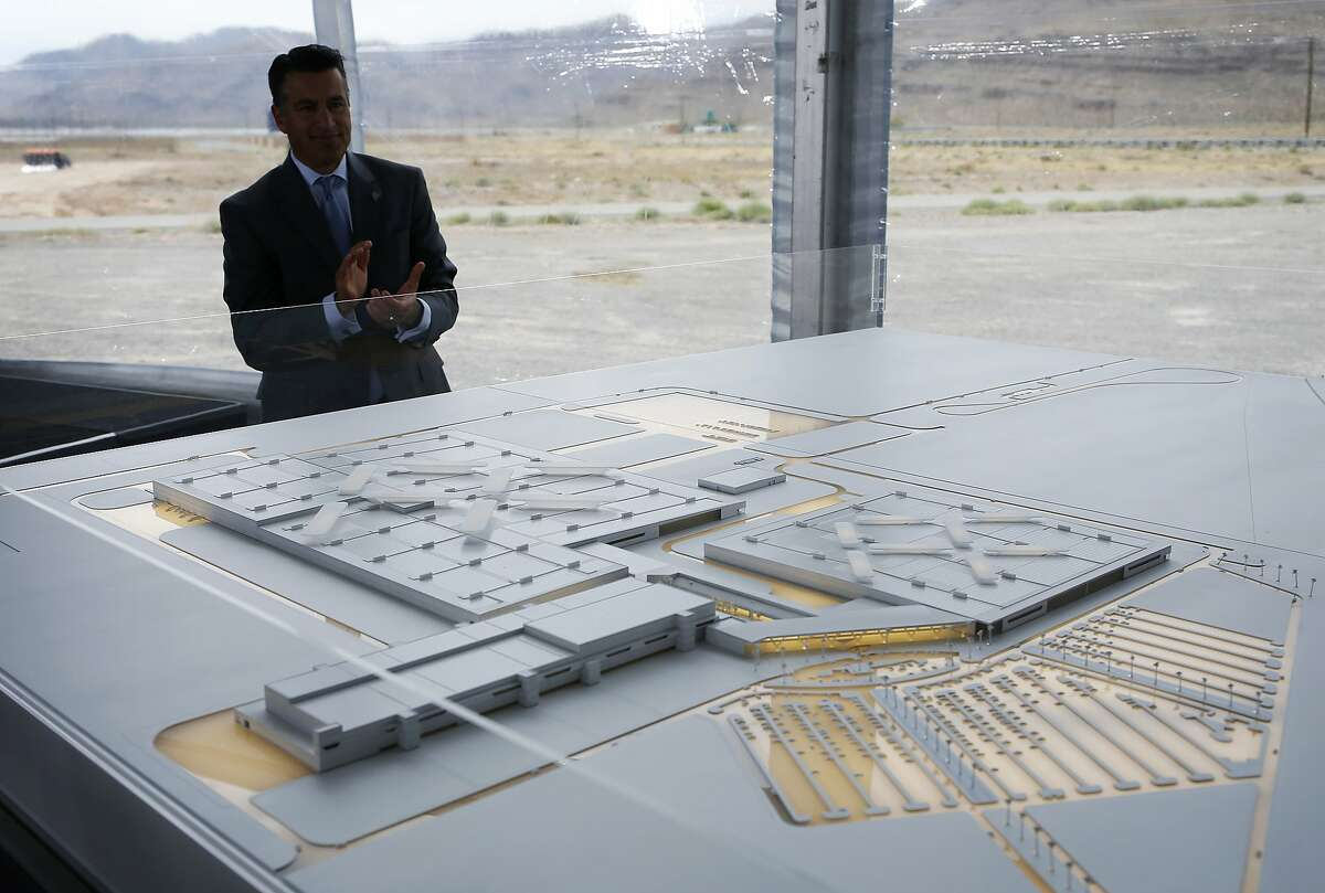FILE - In this April 13, 2016, file photo, Nevada Gov. Brian Sandoval looks at a model for a Faraday Future factory in North Las Vegas, Nev. Work has stopped at a site outside Las Vegas where upstart electric car company Faraday Future has said it plans to have vehicles that are still in the design phase rolling off a new $1 billion assembly line in 2018. Faraday Future spokesman Ezekiel Wheeler said Tuesday, Nov. 15, 2016, the pause after millions of dollars' worth of ground work at the Apex Industrial Park site will let the company put money and attention toward developing the concept car it wants to present at the big Consumer Electronics Show in Las Vegas in January. (AP Photo/John Locher, File)