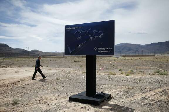 FILE - In this April 13, 2016, file photo, a man walks by a sign at an event to mark the start of construction for Faraday Future in North Las Vegas, Nev. Work has stopped at the site outside Las Vegas where upstart electric car company Faraday Future has said it plans to have vehicles that are still in the design phase rolling off a new $1 billion assembly line in 2018. Faraday Future spokesman Ezekiel Wheeler said Tuesday, Nov. 15, 2016, the pause after millions of dollars' worth of ground work at the Apex Industrial Park site will let the company put money and attention toward developing the concept car it wants to present at the big Consumer Electronics Show in Las Vegas in January. (AP Photo/John Locher, File)
