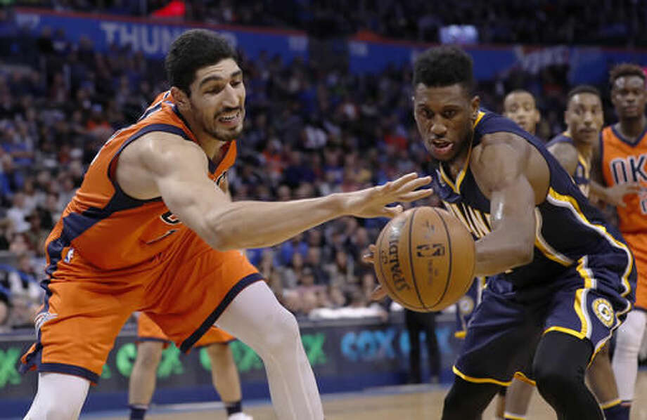 Oklahoma City Thunder center Enes Kanter, left, and Indiana Pacers forward Thaddeus Young, right, go after a loose ball during the second half of an NBA basketball game in Oklahoma City, Sunday, Nov. 20, 2016. Indiana won in overtime 115-111. (AP Photo/Alonzo Adams)